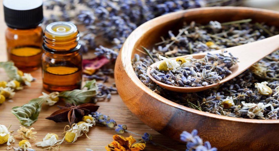 flacons d'huiles essentielles et fleurs de lavande séchées dans un bol en bois