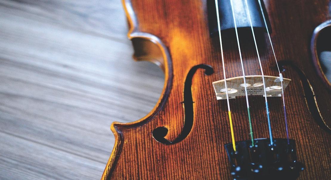 zoom sur les ouïes d'un violon posé sur un plancher en bois brut